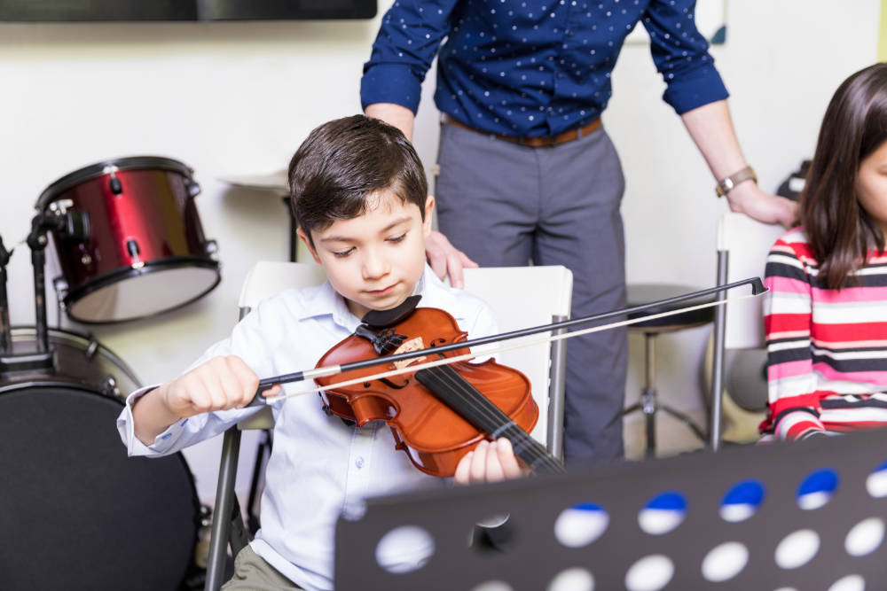 Cute boy concentrating and learning new techniques of playing violin in school